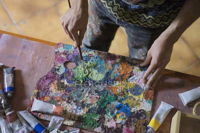 Чоловічий змішування олійних фарб на палітрі художника — стокове фото