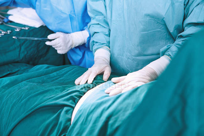 Mid section of surgical team preparing patient's abdomen in maternity ward operating theatre — Stock Photo