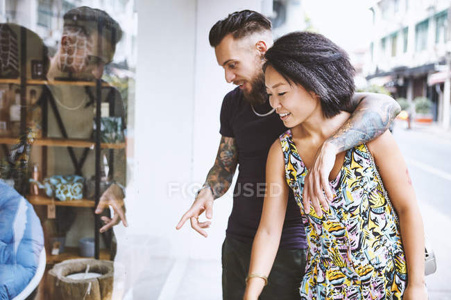 Multi ethnic hipster couple looking and pointing at shop window, Shanghai French Concession, Shanghai, China — Stock Photo