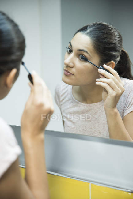 Woman applying mascara in front of mirror — Stock Photo