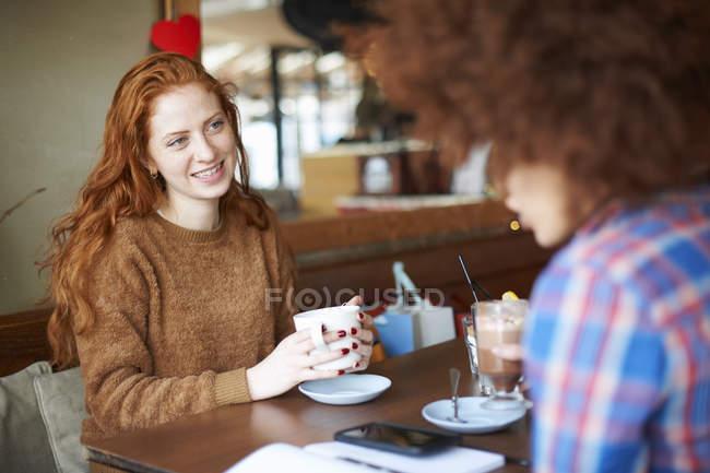 Amis se détendre avec des boissons chaudes dans le café — Photo de stock