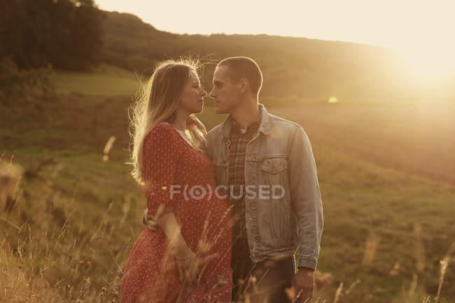 Романтическая беременная пара, стоящая лицом к лицу на склоне холма на закате — стоковое фото