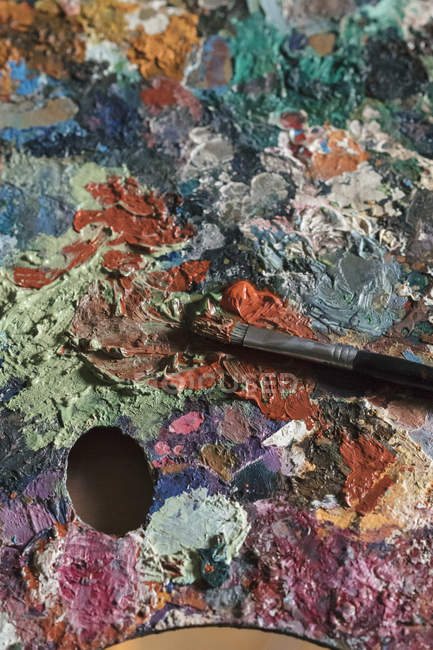 Detail of messy artist palette and paintbrush in artists studio, close up — Stock Photo