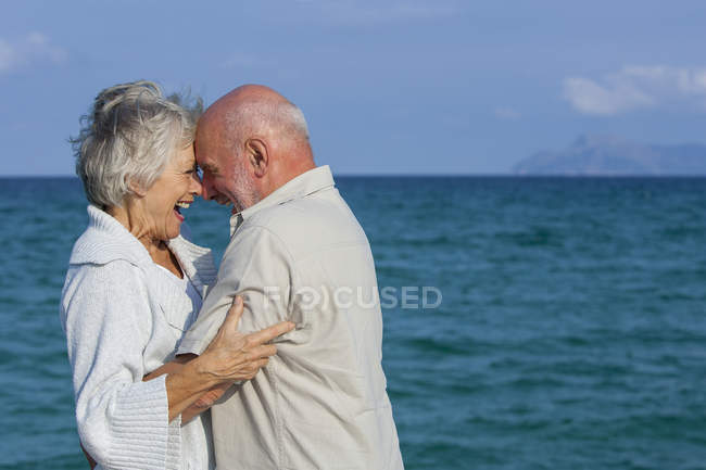 Senior couple hugging and laughing by seaside — Stock Photo