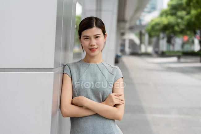 Портрет молодой предпринимательницы, прислонившейся к стене в городе Шанхай, Китай — стоковое фото