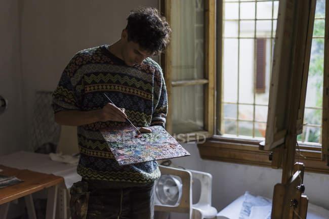 Hombre artista mezcla pinturas al óleo en la paleta en estudio artista - foto de stock