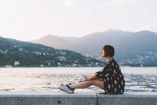 Jovem mulher sentada na parede à beira-mar no Lago de Como, Lombardia, Itália — Fotografia de Stock