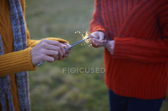 Two young women lighting sparklers — Stock Photo