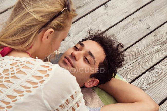 Пара, лежа лицом к лицу на Профнастил — стоковое фото