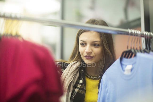 Young woman choosing clothes in shop — Stock Photo