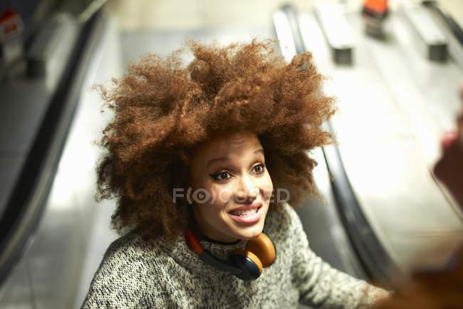 Jeune femme dans les écouteurs souriant sur l'escalator — Photo de stock