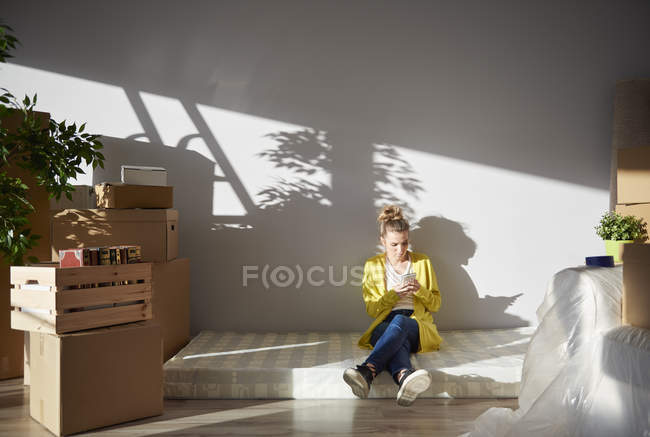 Young woman sitting on mattress in new home and using smartphone — Stock Photo