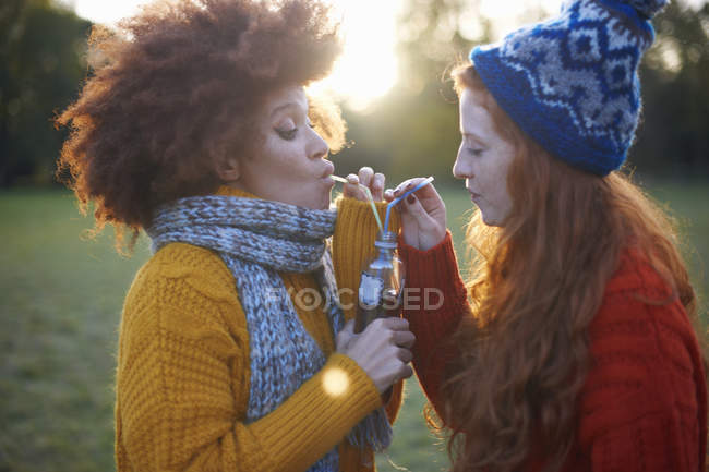 Two young women drinking from bottle with straws — Stock Photo