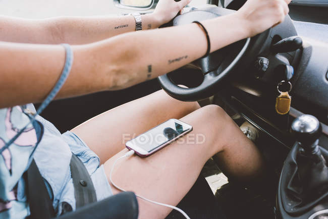 Mid section of young woman driving vehicle with smartphone on her lap — Stock Photo