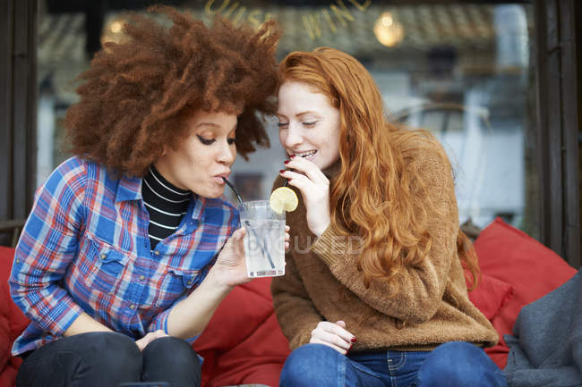 Friends sharing drink through drinking straws — Stock Photo