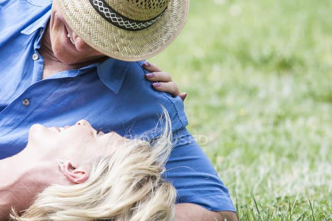 Vista ritagliata della coppia sdraiata sull'erba — Foto stock