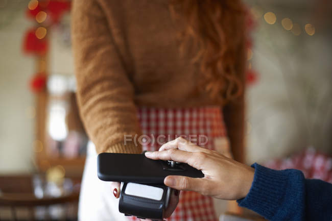 Customer in cafe making contactless payment with mobile phone — Stock Photo