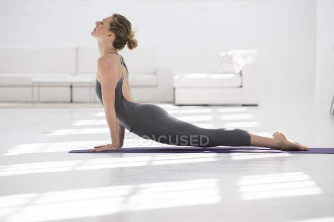 Вид дома женщины в положении йоги сбоку — стоковое фото