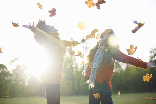 Friends throwing autumn leaves in air — Stock Photo
