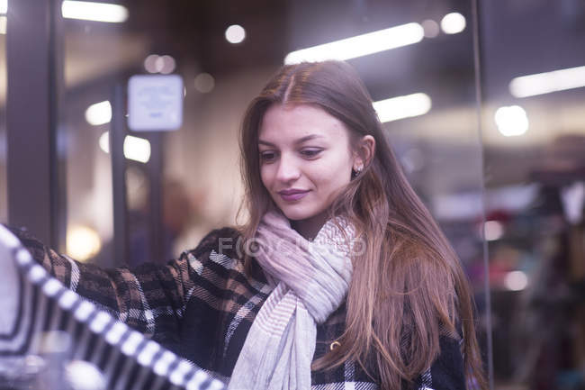 Young woman choosing clothes on shopping — Stock Photo