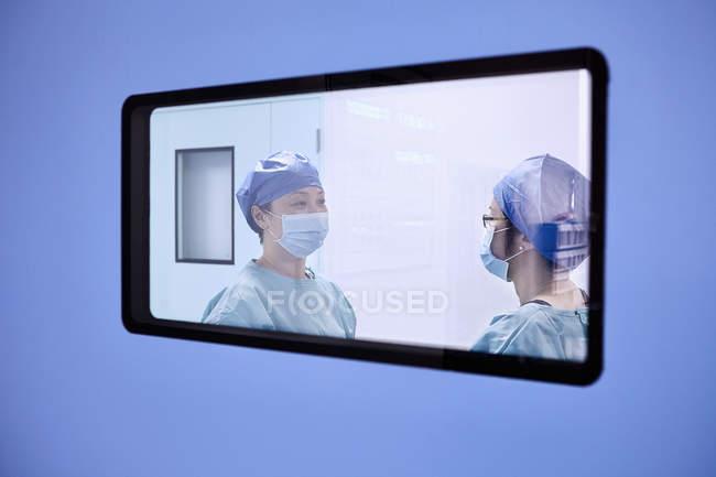 Vista da janela de duas cirurgiãs em discussão na sala de operações da maternidade — Fotografia de Stock