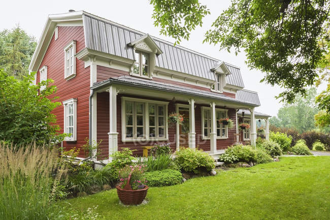 Pinewood plank house facade with mansard roof and landscaped garden, Quebec, Canada — Stock Photo