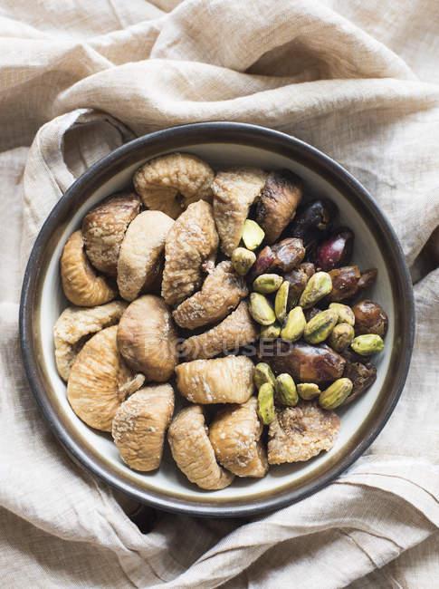 Vue du dessus des fruits secs et des noix dans un bol — Photo de stock