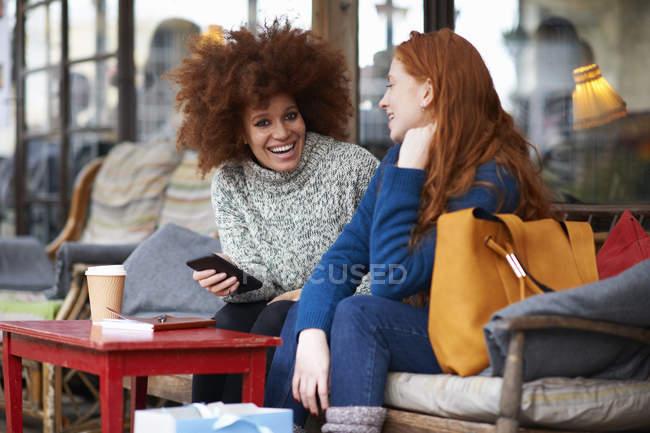 Друзья в кафе используют мобильный телефон и смеются — стоковое фото