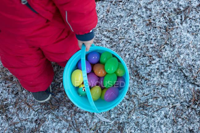 Обітнутого зображення хлопчика, що тримається відро з іграшку яйця — стокове фото