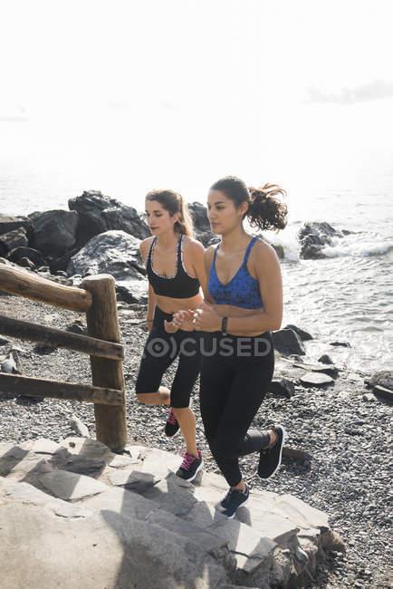 Deux jeunes femmes se précipitent sur l'escalier de la plage — Photo de stock