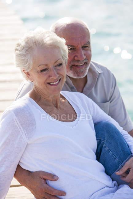 Портрет пожилой пары на деревянном пирсе у моря — стоковое фото