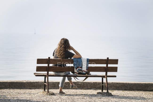 Rückansicht einer Frau, die auf einer Bank sitzt und auf den See blickt — Stockfoto