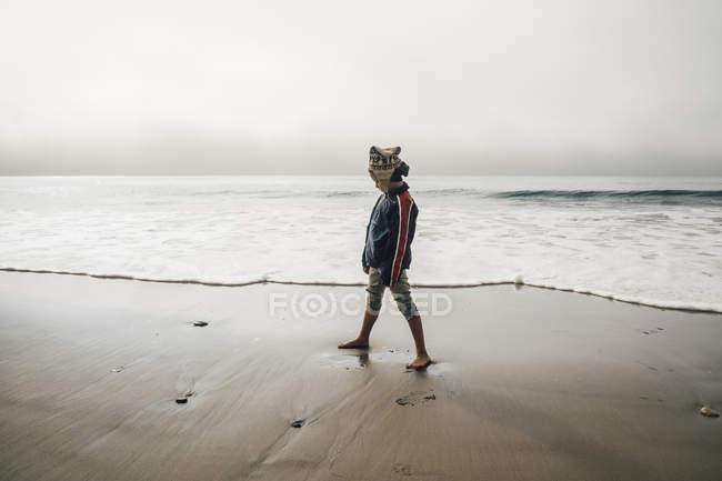 Young boy standing on beach and looking away — Stock Photo