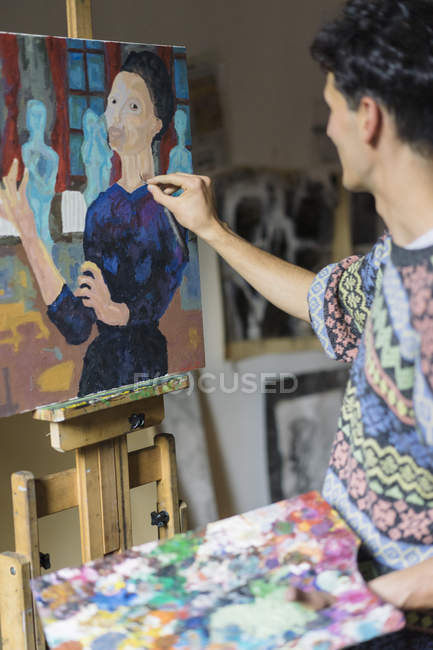 Male artist painting on easel in artist studio — Stock Photo