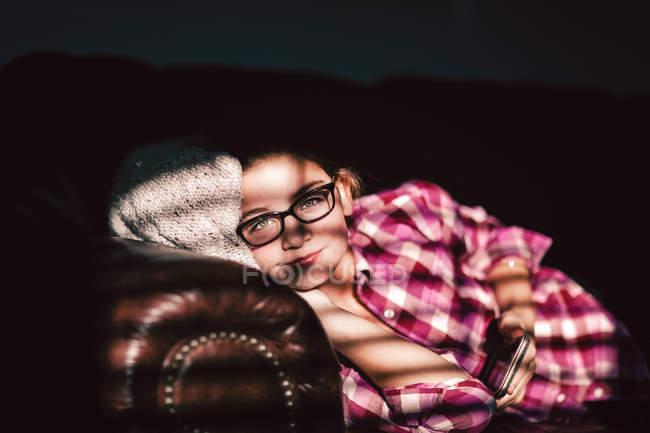 Ragazza rilassante sul divano e in possesso di smartphone — Foto stock