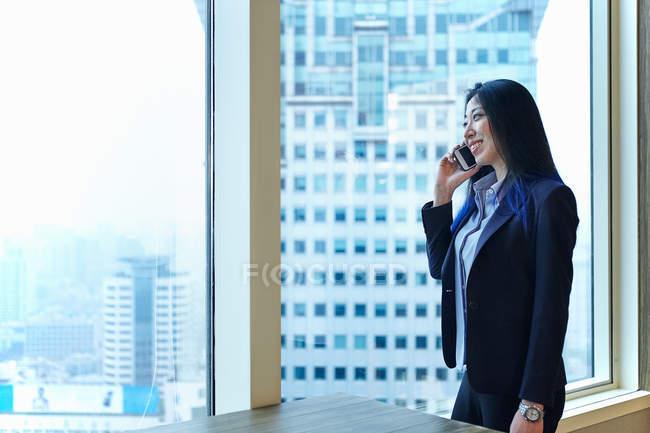 Businesswoman near office window making telephone call — Stock Photo