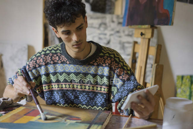 Male artist looking at smartphone while painting canvas in artist studio — Stock Photo