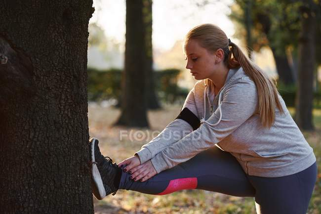 Curvaceous young woman training and touching toes in park — Stock Photo