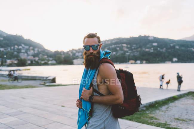 Ritratto di giovane maschio con zaino sul lago di Como, Lombardia, Italia — Foto stock