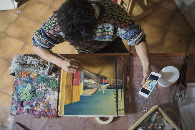 Artist looking at smartphone while painting at canvas in studio — Stock Photo
