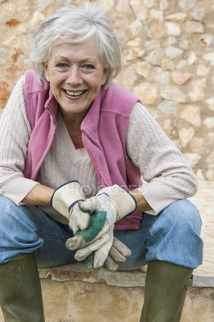Portrait of senior woman outdoors, wearing gardening gloves — Stock Photo