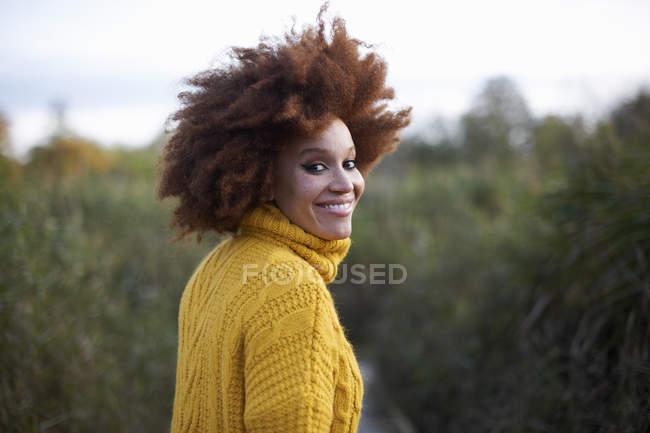 Retrato de mujer con afro sonriendo sobre el hombro a la cámara - foto de stock