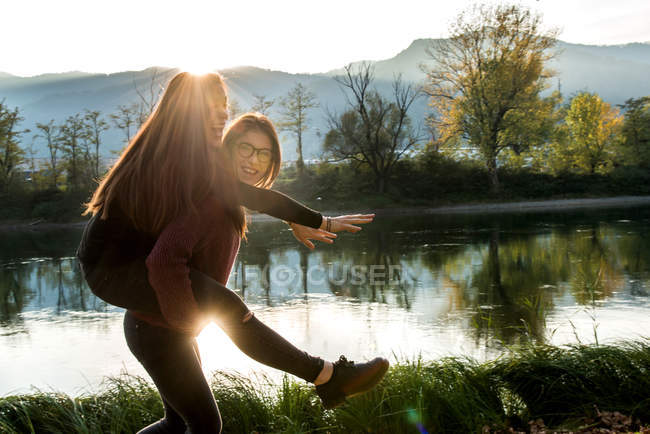 Young woman giving best friend on piggy back near river — Stock Photo