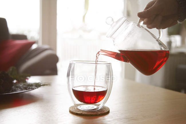 Woman pouring red tea into glass — Stock Photo