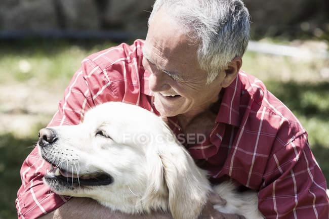 Старший чоловік, обіймати собаку на вулиці. — стокове фото