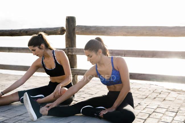 Две молодые женщины тренируются на набережной — стоковое фото