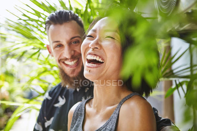 Multi ethnic couple laughing together in residential alleyway, Shanghai French Concession, Shanghai, China — Stock Photo