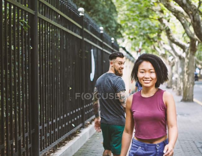Junge männliche Hipster Rückblick auf die Frau auf dem Bürgersteig, Shanghai French Concession, Shanghai, China — Stockfoto