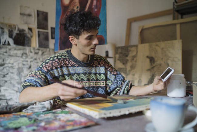 Male artist looking at smartphone while painting at canvas in studio — Stock Photo