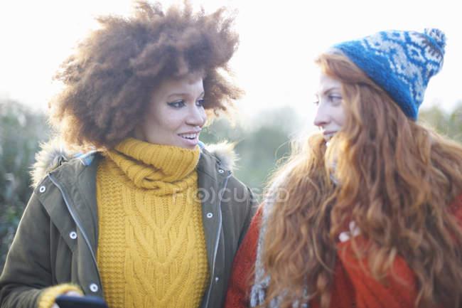 Друзів в теплий одяг посміхаючись лицем до лиця — стокове фото